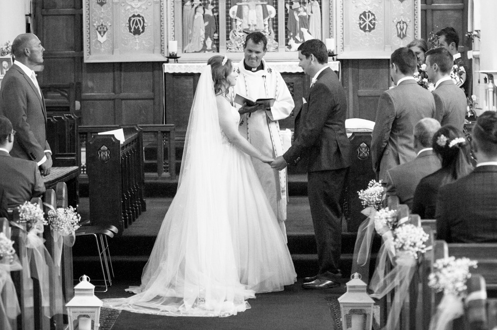 Bride and groom exchanging vows, Burley in Wharfedale church, Yorkshire wedding photographers