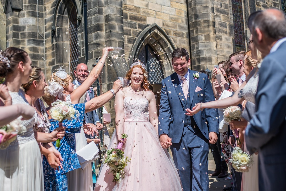 Bride and groom walk through confetti, Burley in Wharfedale church, Yorkshire wedding photographers