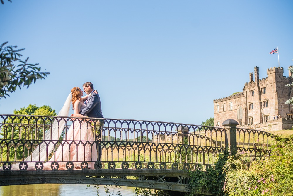 Bride and groom kissing on bridge with castle in background, Ripley Castle weddings, Yorkshire wedding photographers