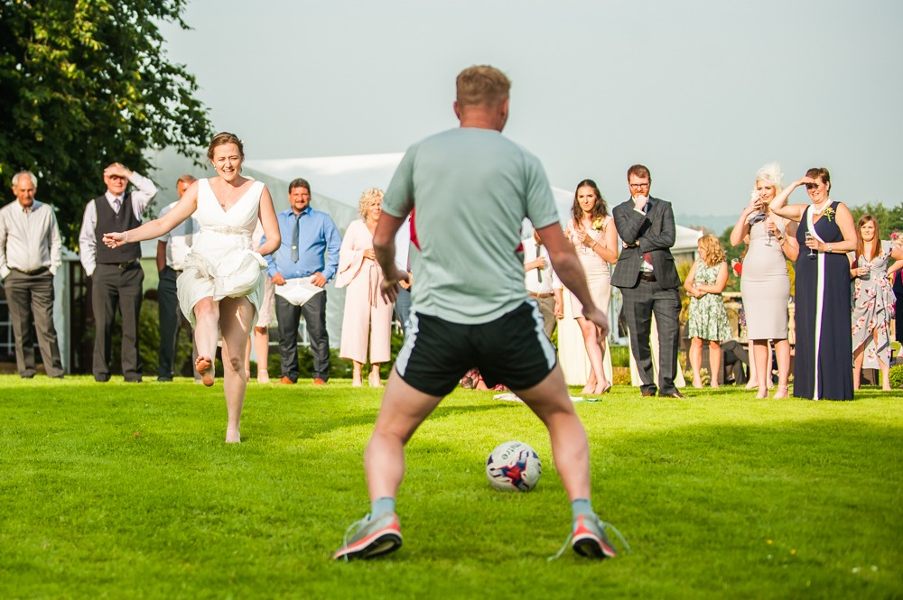 Bride kicking football during wedding penalty shootout, Ringwood Hall weddings, Sheffield wedding photographer
