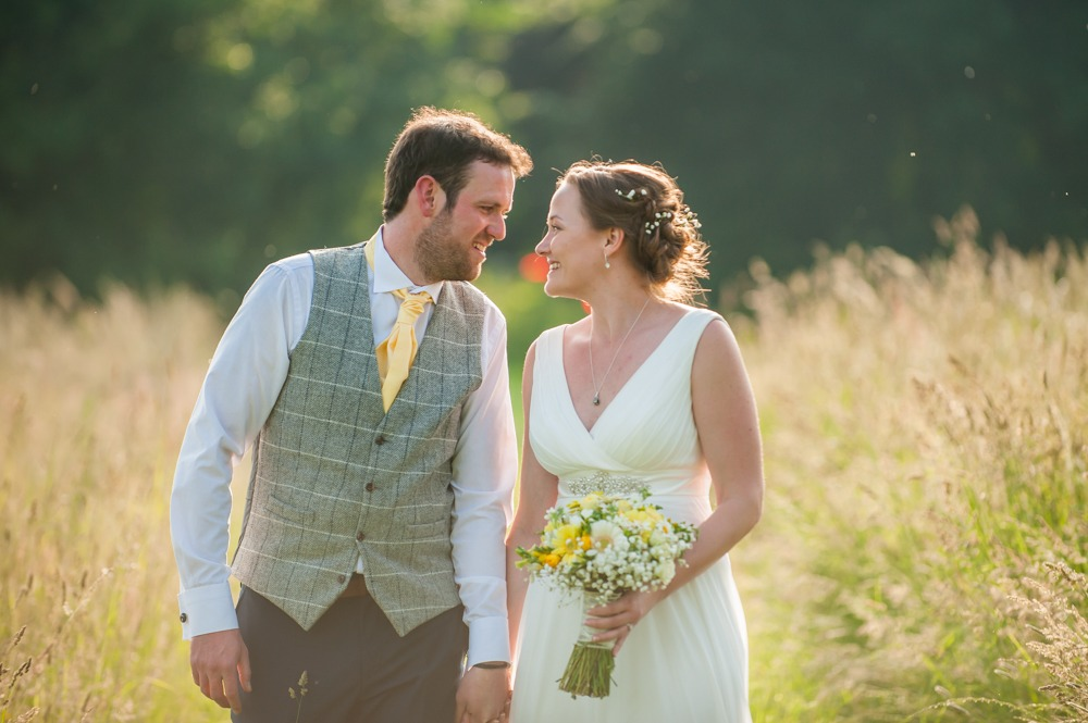 Bride and groom looking at each other walking through long grass, Ringwood Hall weddings, Sheffield wedding photographer