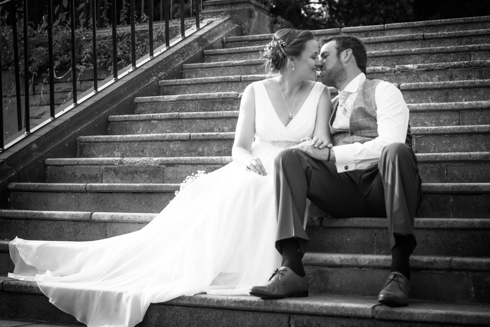 Bride and groom kissing on steps in hotel garden, Ringwood Hall weddings, Sheffield wedding photographer