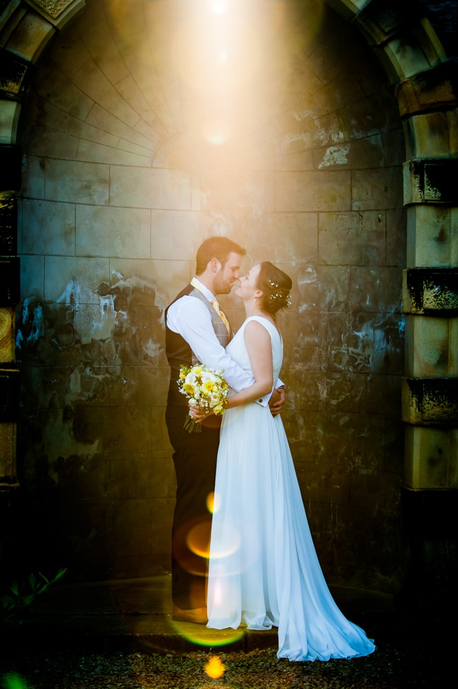 Bride and groom under archway in sunflare, Ringwood Hall weddings, Sheffield wedding photographer