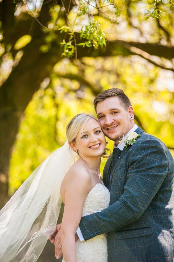 Bride and groom posing under tree in church yard, Wortley Hall, Sheffield wedding photography